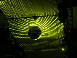 ball with light inside silhouette disco ball hanging at ceiling reflected with green