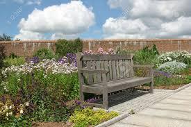 Walled Garden Login by Old Oak Wooden Bench Within A Red Brick Walled Garden In Summer