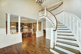 curved staircase in two story foyer with pillars leading to dining