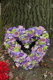 heart shaped sympathy flowers in different shades of purple stock
