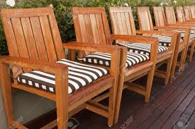 Black And White Striped Chair by A Line Of Teak Wood Chairs With Black And White Striped Cushions