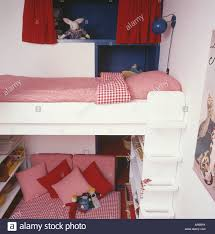 red checked bedlinen on platform bed with white steps above red