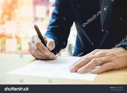 pen writing on paper closeup businessperson signing contractwoman writing paper stock close up of businessperson signing contract woman writing paper at the desk with pen