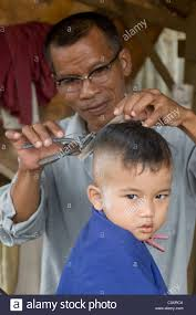 a child gets his hair cut at a roadside barber shop stock photo