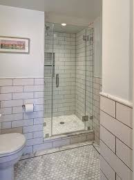 white tiled shower stalls with seats and glass door in the corner