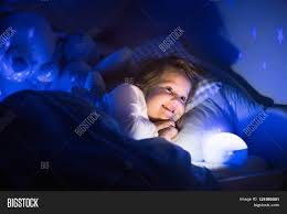 Stars On Ceiling by Little Reading A Book In Bed Dark Bedroom With Night Light