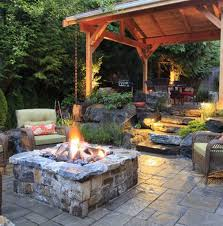 stone fire pit and wooden pergola for superb paved patio design