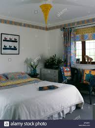 white bedspread and abstract patterned linen and matching curtains