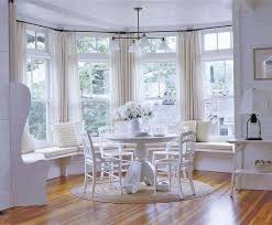 white dining room designed with window benches and white furniture
