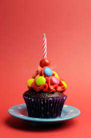 candy covered chocolate cupcake with red frosting and candy and
