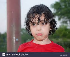hispanic boy with a sad face latin child with wet curly