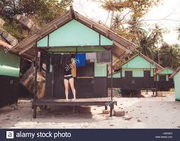 woman hanging clothes to dry outside bungalow on a beach in