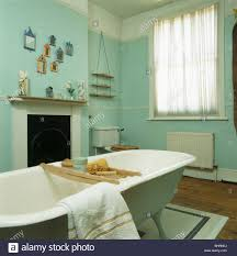roll top bath with wooden bath rack in pale green bathroom with