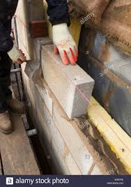 self building house bricklayer laying upper floor concrete block