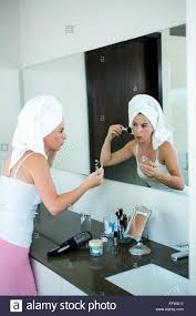 woman applying face powder in the bathroom mirror stock photo