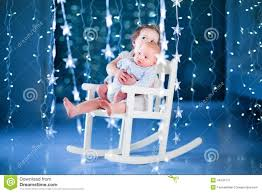 cute toddler and her newborn baby brotherin a dark room with