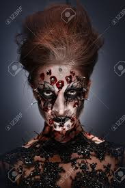 a creepy female halloween makeup of a witch with a bloody face