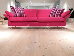 Pink Laminate Flooring A Relaxing Pink Sofa With Pillows On A White Pine Wood Floor Stock