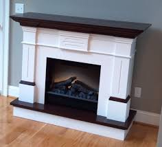white fireplace mantel with black woden top connected by grey wall