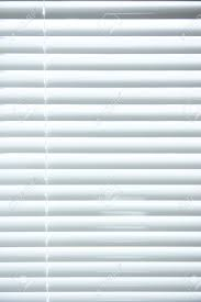 background image of white mini blinds inside home closed stock