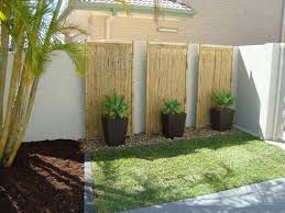 tall planters and rocks against wall lined by stones small