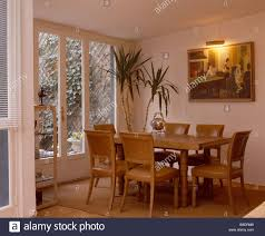 picture light above painting on wall in airy dining room with