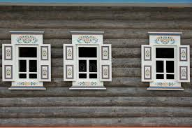 log cabin wall with three ornamental windows stock photo image
