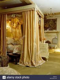 four post bed opulent cream silk drapes on four poster bed in countgry bedroom