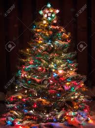 snow covered tree with multi colored lights stock photo