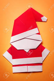 origami santa claus paper craft on orange background stock photo