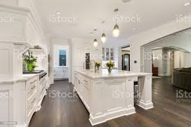 images white kitchen cabinets wood floors all white kitchen with brown wood flooring stock photo image now