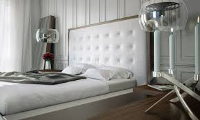 bedroom white tufted headboard with pretty rug and white wall for