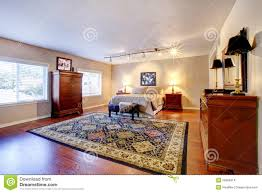 large bedroom with hardwood floor and two dressers stock images