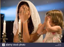 mother and daughter blessing on shabbat candles stock photo