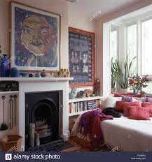 large picture above fireplace in bedroom with pink cushions and