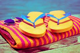 flip flop towel sunglasses flip flops and towel on a wooden boardwalk