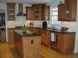 maple cabinets with black island solid surface countertops kitchens with black flooring lighting