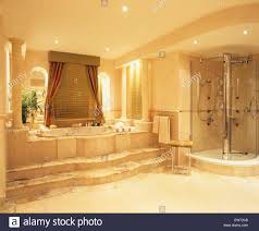 steps up to bath in marble spanish bathroom with a glass corner