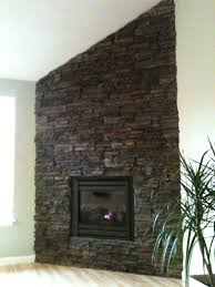 corner drystack stone fireplace adjacent to a vaulted ceiling