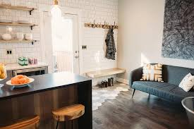 kitchen opens to mudroom with blond wood floating bench and row of