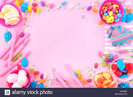 background with decorated borders of bright colorful candy on pink