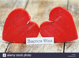 buenos dias good morning in spanish with two red wooden hearts