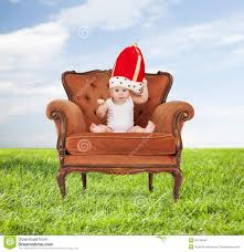 Infant Armchair Baby In Royal Hat With Lollipop Sitting On Chair Stock Photo