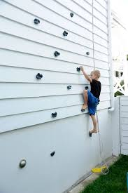 a kids climbing wall on the side of a house love it for the