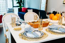 thanksgiving table set up place settings gold blue orange bows