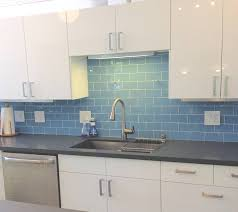 blue glass subway tile backsplash white cabinets in kitchen