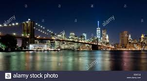 the new york city skyline at night w brooklyn bridge and freedom