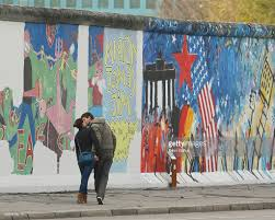 berlin s east side gallery reopens after face lift photos and a couple kiss while walking by restored murals along a still existing portion of the