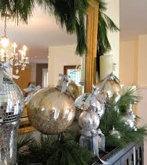 decorating a mantel with evergreen garland and mercury glass