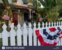 Picket Fences Picket Fence In Front Of House With Us Flags And Bunting Stock